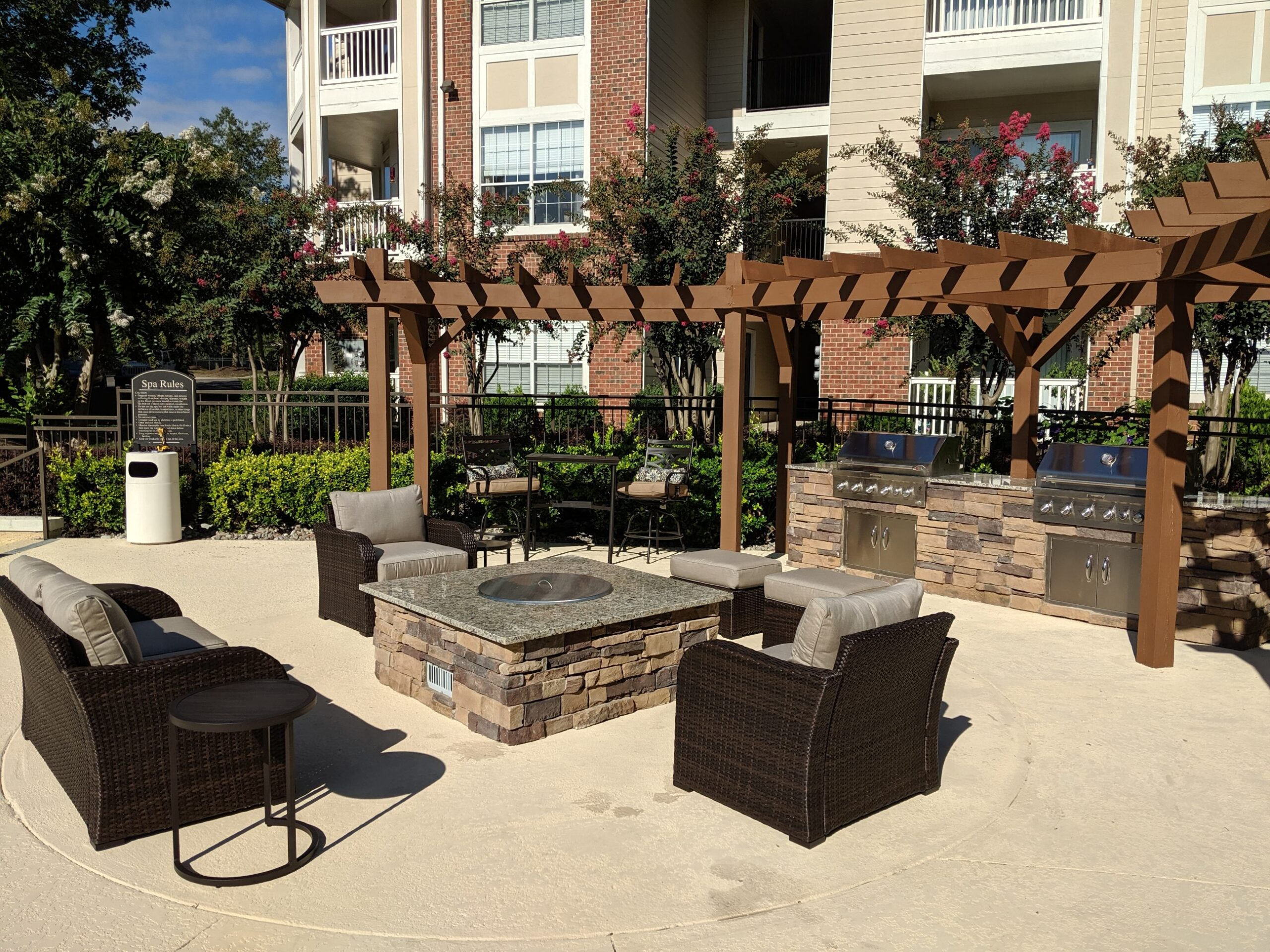 Ashborough apartment's fire pit surrounded by faux rattan lawn furniture. nearby is a two station outdoor grill under a wooden pergola